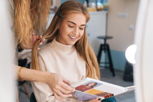Een gelukkige jonge mooie vrouw cliënt met kapper in salon.