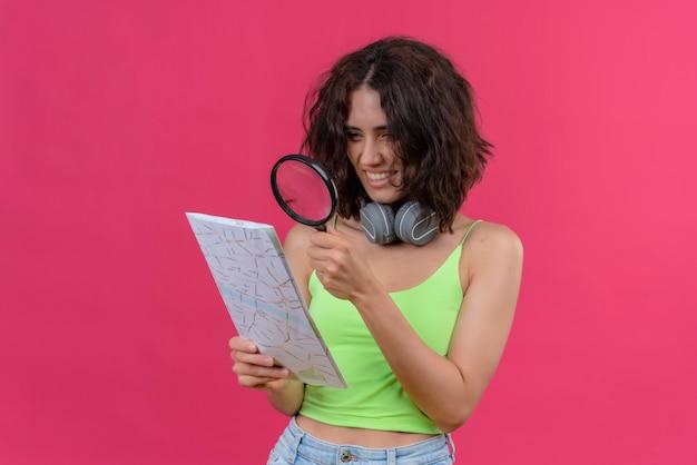 Een gelukkige jonge mooie vrouw met kort haar in een groene crop top in koptelefoon kijken naar een kaart met vergrootglas