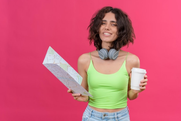 Een gelukkige jonge mooie vrouw met kort haar in groene crop top in koptelefoon met plastic kopje koffie en