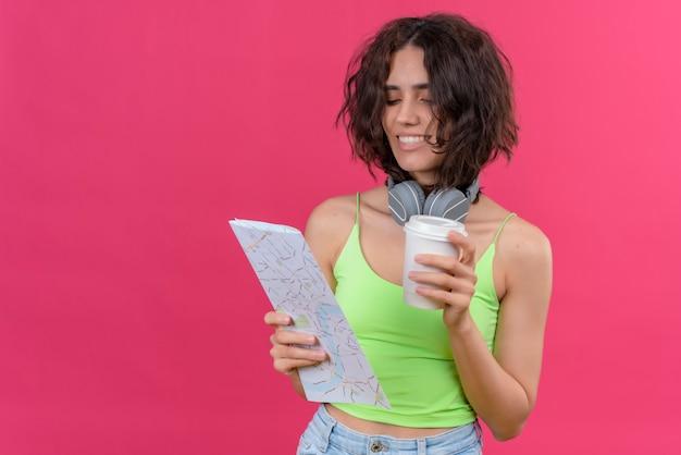 Een gelukkige jonge mooie vrouw met kort haar in groene crop top in koptelefoon met plastic kopje koffie kijken naar kaart