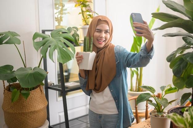 Een gelukkige jonge moslimvrouw die selfie maakt met haar planten en thuis videogesprekken voert