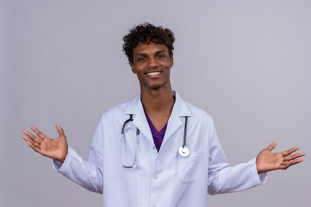 Een gelukkige jonge opgewonden knappe donkere mannelijke arts met krullend haar die witte laag met stethoscoop dragen die zijn handen opent