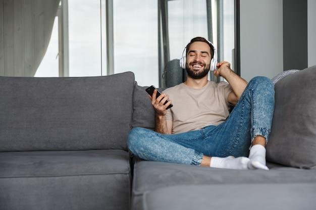 Een gelukkige jonge positieve man binnenshuis thuis op de bank muziek luisteren met een koptelefoon met behulp van mobiele telefoon.