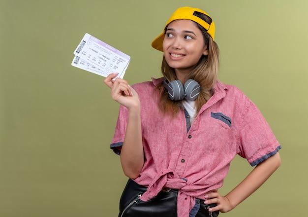Een gelukkige jonge vrouw die een rood overhemd en een gele honkbalhoed met hoofdtelefoons draagt die vliegtickets toont terwijl zij op een groene muur kijkt