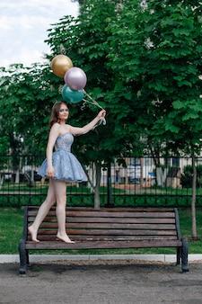 Een gelukkige jonge vrouw in een blauwe korte korsetjurk loopt blootsvoets op een bankje en houdt vliegende ballonnen vast...