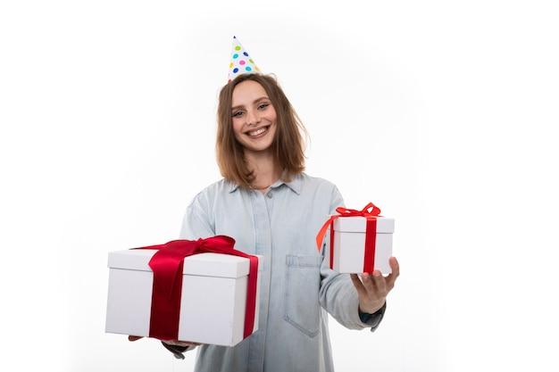 Een gelukkige jonge vrouw in een feestelijke hoed heeft twee geschenken op een witte achtergrond