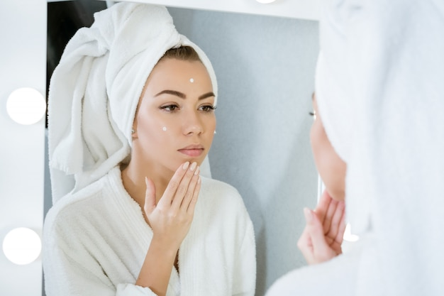 Een gelukkige jonge vrouw in een handdoek voor een spiegel past crème toe op haar gezicht, een concept van huidzorg thuis