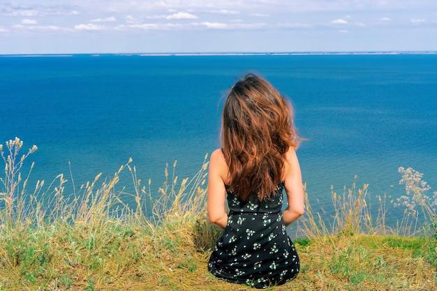 Een gelukkige jonge vrouw in een jurk zit op een klif met de blauwe zee voor haar