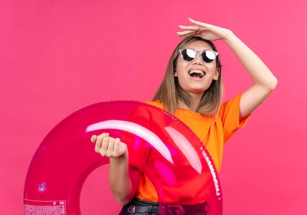Een gelukkige jonge vrouw in een oranje t-shirt met een zonnebril die glimlacht en ver weg kijkt terwijl ze een roze opblaasbare ring op een roze muur houdt