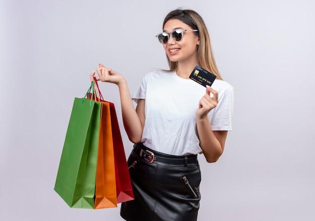 Een gelukkige jonge vrouw in wit t-shirt die zonnebril draagt die creditcard toont terwijl zij boodschappentassen op een witte muur houdt