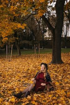 Een gelukkige jonge vrouw met een rode jurk en zwarte hoed poseren in het stadspark in de herfstdagmodus...