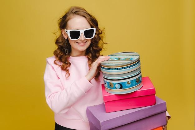 Een gelukkige jonge vrouw met kleurrijke kartonnen dozen na het winkelen geïsoleerd op een oranje achtergrond studio. seizoensuitverkoop, aankopen, geld uitgeven aan geschenken.