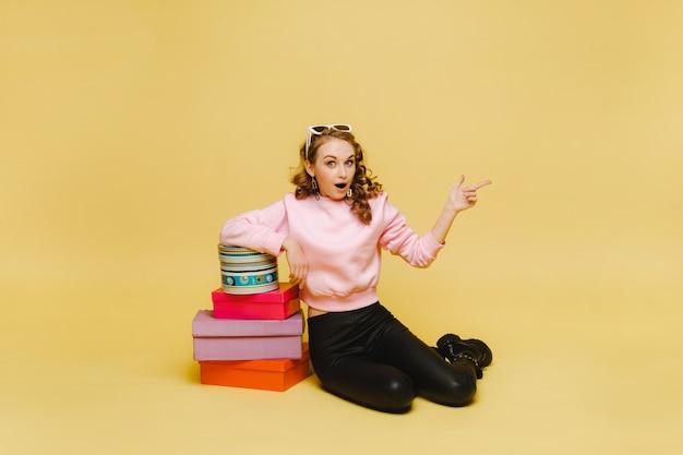 Een gelukkige jonge vrouw met kleurrijke kartonnen dozen na het winkelen geïsoleerd op een oranje achtergrond studio