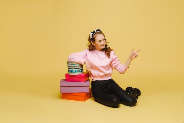 Een gelukkige jonge vrouw met kleurrijke kartonnen dozen na het winkelen geïsoleerd op een oranje achtergrond studio.