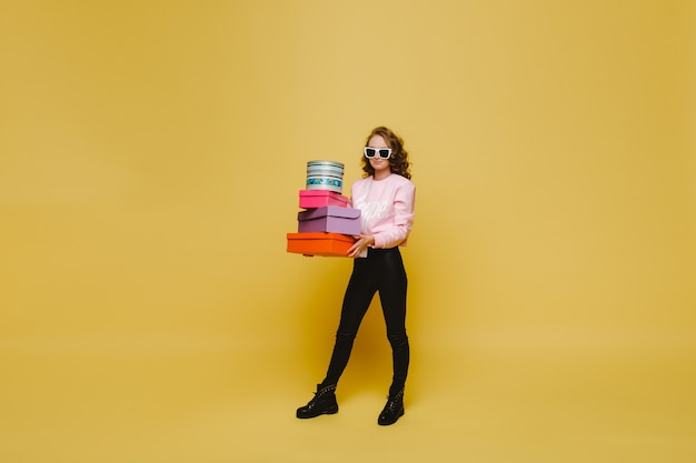 Een gelukkige jonge vrouw met kleurrijke kartonnen dozen na het winkelen geïsoleerd op een sinaasappel