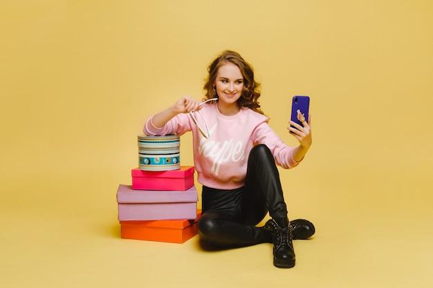 Een gelukkige jonge vrouw met kleurrijke kartonnen dozen na het winkelen, zitten en het nemen van selfies geïsoleerd op een oranje studio-achtergrond.