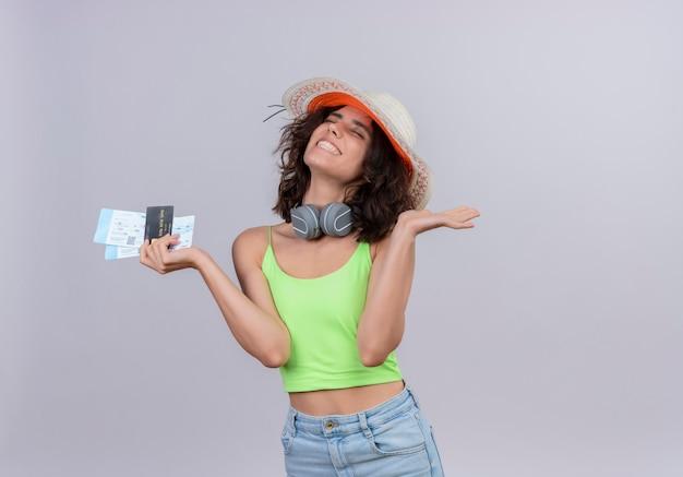 Een gelukkige jonge vrouw met kort haar in een groene crop top dragen zonnehoed met vliegtickets en een creditcard op een witte achtergrond