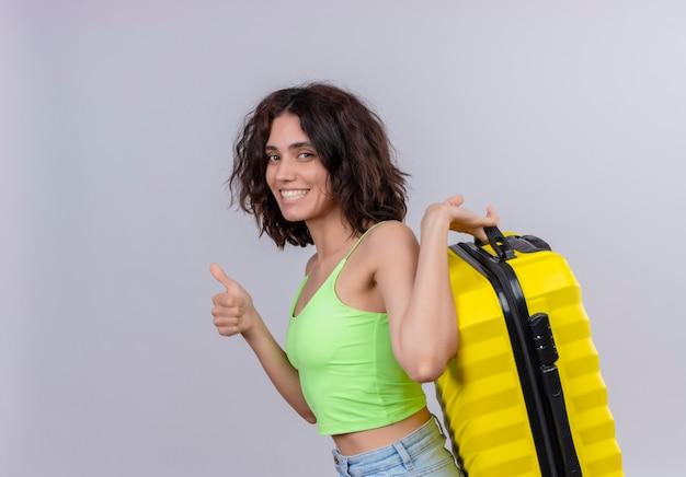 Een gelukkige jonge vrouw met kort haar in een groene crop top glimlachend en met gele koffer op een witte achtergrond