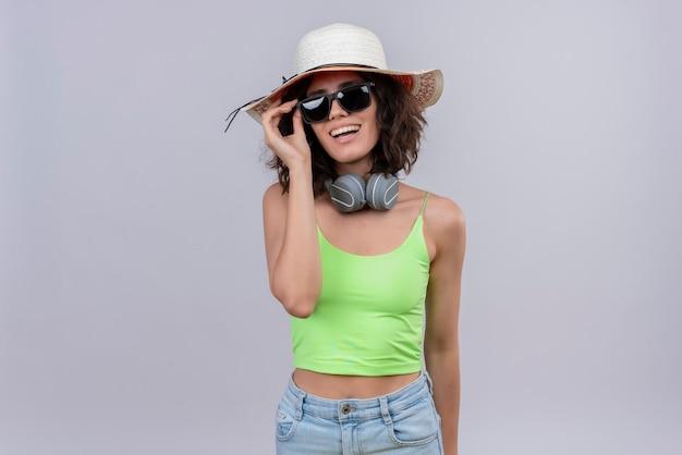 Een gelukkige jonge vrouw met kort haar in een groene crop top in koptelefoon met zonnebril en zonnehoed op een witte achtergrond