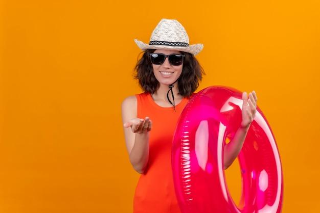 Een gelukkige jonge vrouw met kort haar in een oranje overhemd dat zonnehoed en zonnebril draagt die opblaasbare ring houdt die dichterbij met handgebaar roept