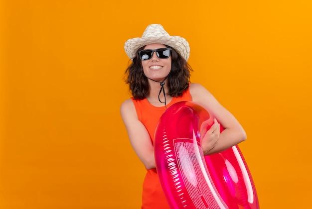 Een gelukkige jonge vrouw met kort haar in een oranje overhemd dat zonnehoed en zonnebril draagt die opblaasbare ring houdt