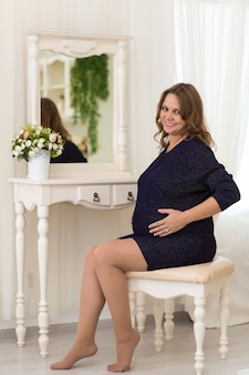 Een gelukkige jonge zwangere vrouw zit aan de kaptafel tegenover de spiegel