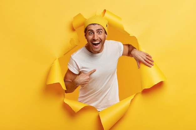 Een gelukkige jongeman wijst naar zichzelf, drukt zijn verwondering uit dat hij is gekozen, glimlacht breed, draagt vrijetijdskleding