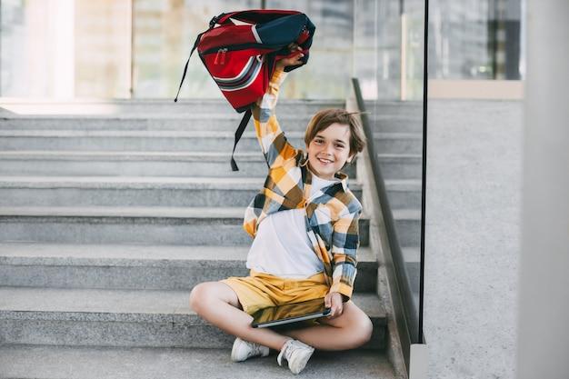 Een gelukkige jongen in glazen met een rugzak en een tablet zit op de trap bij de ingang van de school