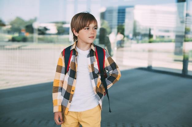 Een gelukkige jongen met een rugzak staat bij de school, glimlacht prachtig en kijkt bedachtzaam in de verte