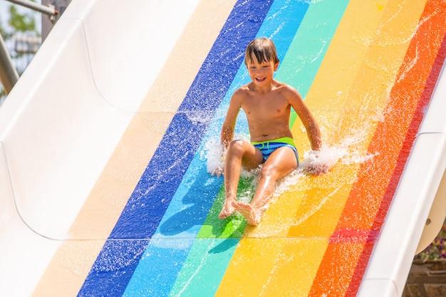 Een gelukkige jongen op glijbaan in een zwembad met plezier tijdens de zomervakantie in een prachtig aquapark. een jongen die van de glijbaan afglijdt en spetters maakt.