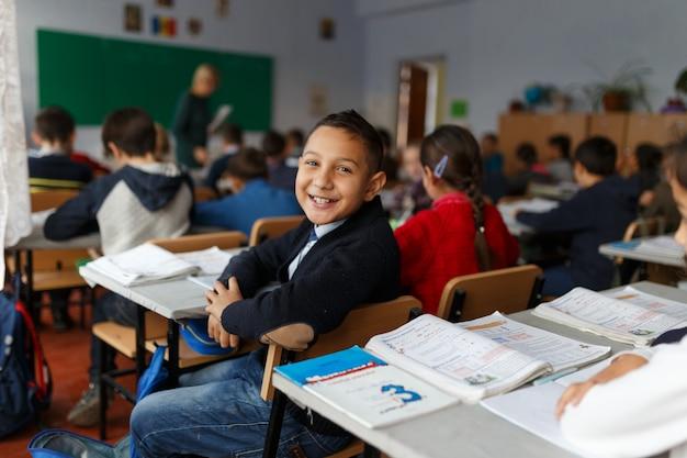 Een gelukkige jongen op zijn eerste schooldag