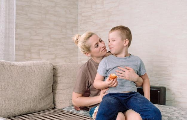 Een gelukkige jongen zit bij zijn moeder op schoot en eet een heerlijke cake. gezinsgeluk