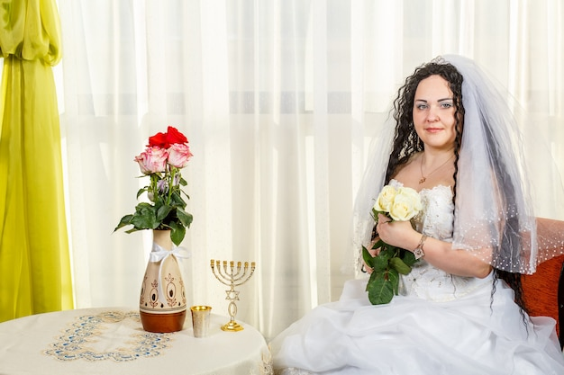 Een gelukkige joodse bruid met een boeket witte rozen zit in de synagoge voor de huppa-ceremonie aan een tafel met bloemen en een menora. horizontale foto.