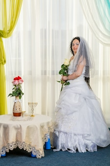 Een gelukkige joodse bruid staat in de hal voor de chuppa-ceremonie aan een tafel met bloemen met een boeket witte rozen in haar handen. verticale foto