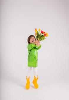 Een gelukkige kleine jongen in een groene regenjas en gele rubberen laarzen heeft een boeket van kleurrijke tulpen op een witte achtergrond met een plek voor tekst