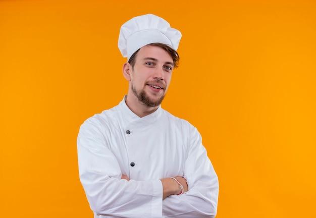 Een gelukkige knappe jonge bebaarde chef-kok man in wit uniform hand in hand gevouwen terwijl hij op een oranje muur keek
