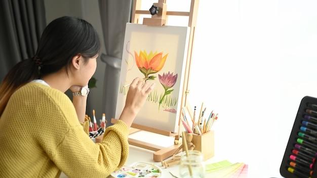 Een gelukkige kunstenaar zit op de vloer en schildert op ezel op haar werkruimte