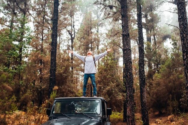 Een gelukkige man die geniet van de natuur en bomen in het bos die met zijn auto of voertuig plezier maakt
