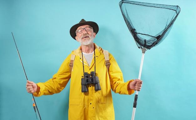 Een gelukkige man, een oude man met een baard in een hoed en een bril, gekleed in een felgele mantel, een regenjas verzameld voor een visreis
