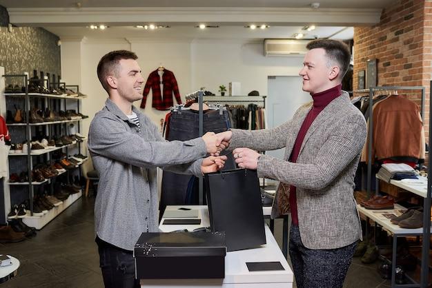 Een gelukkige man neemt zijn aankoop en schudt de hand van een glimlachende winkelbediende in een kledingwinkel.
