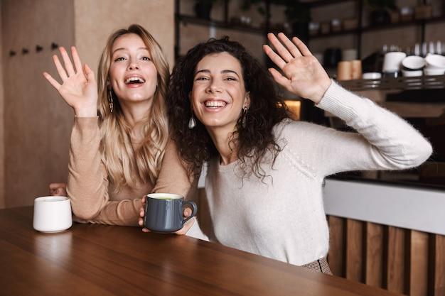 Een gelukkige meisjesvriend die in café met elkaar zit te praten en thee of koffie drinkt zwaaiend