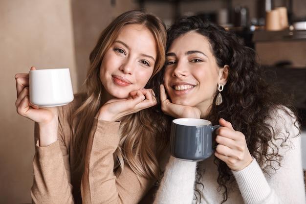 Een gelukkige meisjesvriend die in café met elkaar zit te praten en thee of koffie drinkt