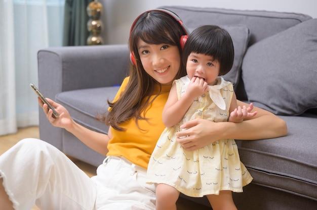 Een gelukkige moeder en dochter die naar muziek luisteren en thuis ontspannen
