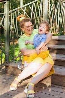 Een gelukkige moeder en een gehandicapt kind zitten op het gras in het park en knuffelen zachtjes. zomervakantie. onbekwaamheid.
