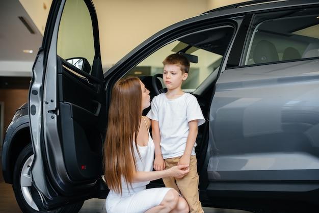 Een gelukkige moeder kiest met haar zoontje een nieuwe auto bij een autodealer. een auto kopen.