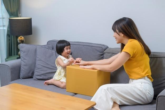Een gelukkige moeder met dochter die een kartonnen doos in de woonkamer thuis opent