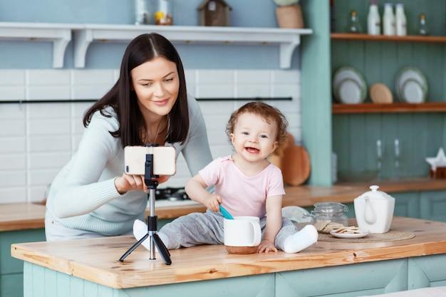 Een gelukkige moeder met een kind zit in de keuken aan tafel en schrijft video voor de blog op een smartphone die op een statief is bevestigd