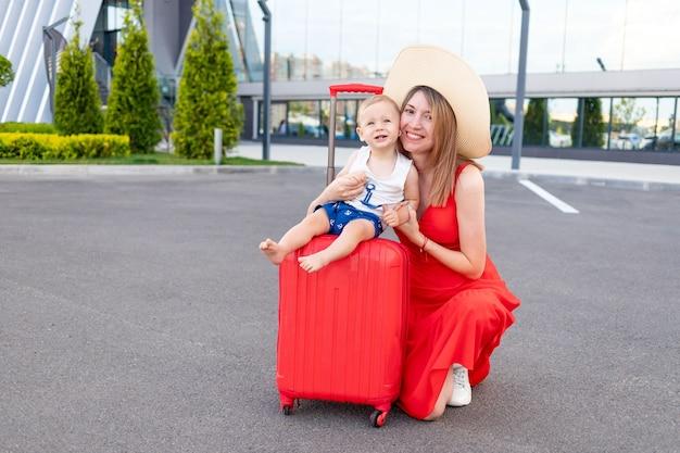 Een gelukkige moeder met een zoontje op het vliegveld met een rode koffer gaat in de zomer op reis of op vakantie