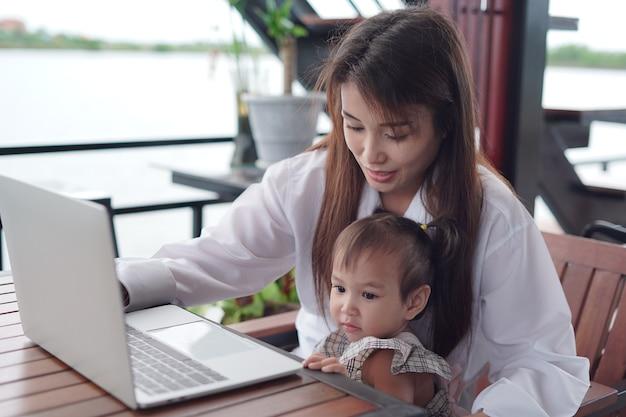 Een gelukkige moeder met haar kind zittend op een computer. goede relatie met moeder en zoon.