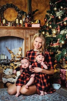 Een gelukkige moeder met haar tweelingkinderen in het nieuwjaarsinterieur van het huis op de achtergrond van een kerstboom